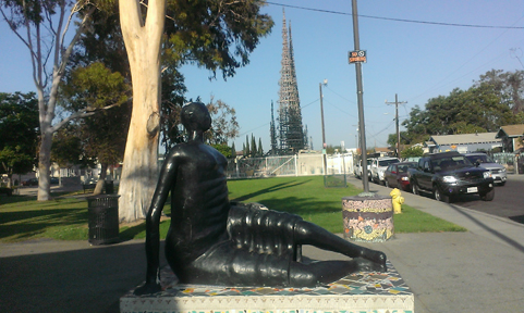 Statue with Watts Towers in Background